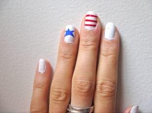 Дизайн ногтей в домашних условиях, белый маникюр матовым лаком с красными полосками и синими звездами